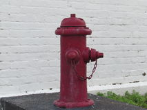 Vieille bouche d'incendie rouge contre le mur de briques blanc images stock
