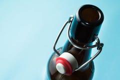 Vieille bouteille brune avec de la bière sans label d'isolement sur un fond bleu photographie stock libre de droits