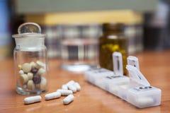 Vieille bouteille de pilules avec quelques pilules Image stock