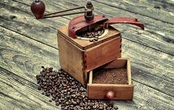 Vieille broyeur de café avec le cafè moulu Photos stock
