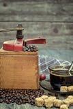 Vieille broyeur de café avec une tasse de café Photographie stock