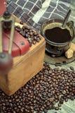 Vieille broyeur de café avec une tasse de café Images stock