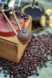Vieille broyeur de café avec une tasse de café Photo stock