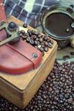 Vieille broyeur de café avec une tasse de café Photo libre de droits