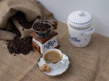 Vieille broyeur de café avec une tasse de café, des grains de café dans un sac à café et de la boîte de café vue d'en haut photos libres de droits