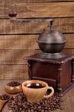 Vieille broyeur de café en bois et grains de café rôtis sur une table en bois Café chaud frais dans la tasse Image libre de droits