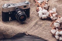 Vieille caméra sur la toile de jute avec du coton photos stock