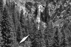 Vieille carlingue de rondin abandonnée avec la cascade image stock