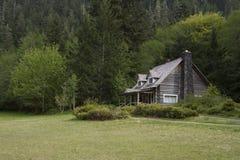 Vieille carlingue de rondin de flanc de montagne Photo libre de droits