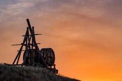 Vieille catapulte en bois sur le fond de ciel de coucher du soleil photo libre de droits