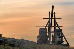 Vieille catapulte en bois sur le fond de ciel de coucher du soleil photographie stock
