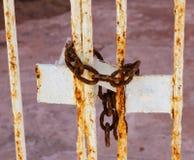 Vieille chaîne rouillée fermant à clef la porte détériorante en métal image stock