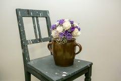 Vieille chaise avec les fleurs blanches et violettes Photographie stock