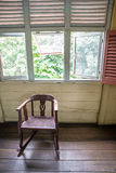 vieille chaise de basculage sous plusieurs fenêtres Photo libre de droits