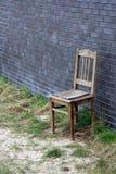 Vieille chaise en bois contre le mur de briques Image libre de droits