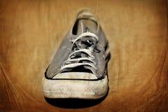 Vieille chaussure avec l'habillement sans abri minable porté par dentelles Photographie stock libre de droits
