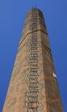 Vieille cheminée de brique rouge (angle faible tiré) avec l'échelle Image stock