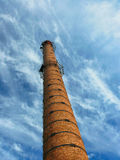 Vieille cheminée industrielle de brique sur le ciel bleu Photographie stock