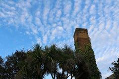 Vieille cheminée méditerranéenne avec les palmiers et le ciel bleu à l'arrière-plan photographie stock