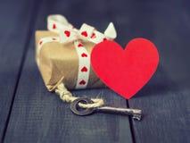 Vieille clé et présents de coeur de papier rouge sur un fond en bois foncé Jour du ` s de St Valentine Copiez l'espace Photos stock