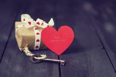 Vieille clé et présents de coeur de papier rouge sur un fond en bois foncé Jour du ` s de St Valentine Copiez l'espace Photo libre de droits