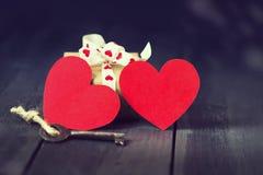 Vieille clé et présents de coeur de papier rouge sur un fond en bois foncé Jour du ` s de St Valentine Copiez l'espace Image libre de droits