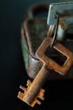 Vieille clé rouillée et serrure en métal sur le fond foncé Images stock