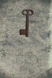 Vieille clé sur le vieux papier texturisé avec les modèles naturels photographie stock