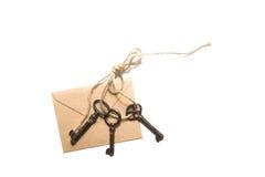 Vieille clé trois et enveloppe sur un fond blanc Image stock