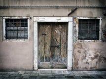 Vieille course fanée en bas de maison vide à Venise avec les murs criqués et boulonnée épluchant la porte en bois avec des barres image libre de droits