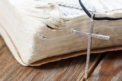 Vieille croix chrétienne argentée sur la bible Photos stock