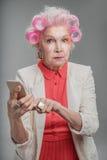 Vieille dame élégante à la mode tenant le téléphone portable Image stock
