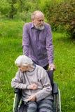 Vieille dame avec la d?mence dans un fauteuil roulant et un soignant images stock