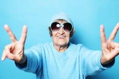 Vieille dame drôle utilisant le chandail, le chapeau bleu et les lunettes de soleil montrant le signe de victoire photos stock