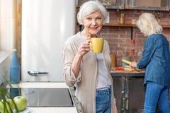 Vieille dame gaie appréciant la boisson chaude dans la cuisine Photo stock