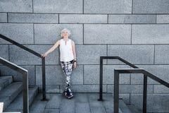Vieille dame gaie détendant après exercice sur les escaliers granitiques dehors Photo stock