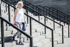 Vieille dame joyeuse retournant à la maison après avoir formé en bas des étapes dehors Images libres de droits