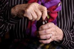 Vieille dame ouvrant une bouteille de médecine Photo stock