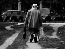 Vieille dame retournant à la maison de l'épicerie photo libre de droits