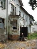 Vieille dame s'asseyant sur le porche de la maison ruinée dans le quartier défavorisé photo libre de droits