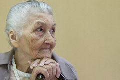 Vieille dame triste contemplant avec le bâton de marche Photos libres de droits