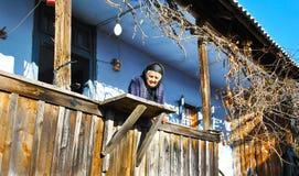 Vieille dame triste sur son porche traditionnel photo stock
