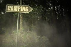 Vieille enseigne avec le camping des textes près de la forêt sinistre image libre de droits