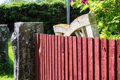 Vieille entrée âgée de jardin se penchant vers une barrière rouge Photo libre de droits