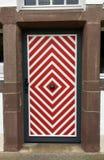 Vieille entrée principale en bois avec la peinture rouge et blanche Photographie stock