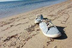 Vieille espadrille bleue sur la plage Images libres de droits