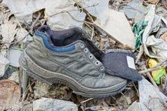 Vieille espadrille grise au sol parmi les déchets Images libres de droits