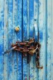 Vieille et colorée porte métallique bleue et fermé avec la chaîne rouillée Photo libre de droits