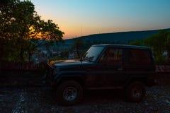 Vieille et sale voiture de Suv au lever de soleil dans la ville de touristes La Roumanie, Sighisoara 2016 Image libre de droits