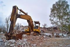 Vieille excavatrice sur les ruines d'une vieille maison Image stock
